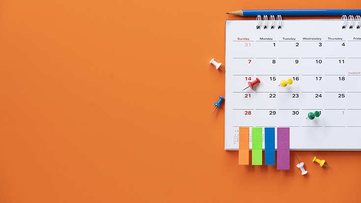 A paper calendar on an orange wall